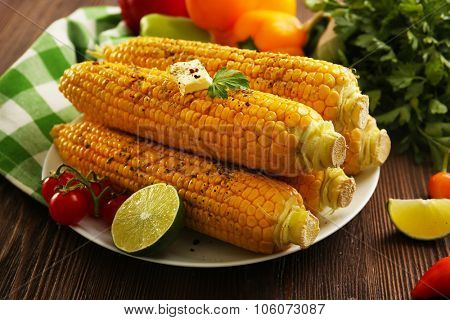 Appetizing grilled corn served with vegetables and green plaid pattern napkin