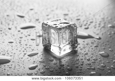 Clear melting ice cube with drops around, close up
