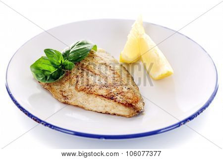 Dish of fish fillet with basil and lemon on plate isolated on white