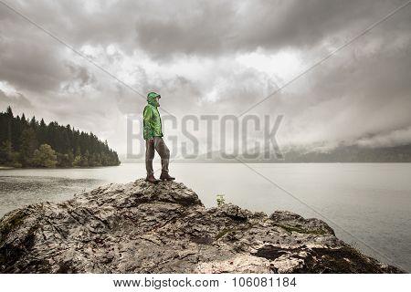 Man Standing On A Rock Beside A Mountain Lake In Rain