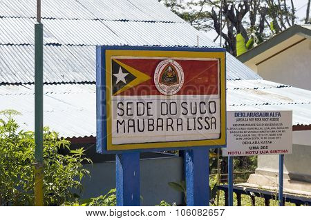 Sign On Maubara Lissa Municipality Headquarters With Timorese Flag, Coat Of Arms And A Sign Enumerat