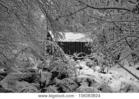 Old Black Wooden House Mill Mill With A Wooden Wheel Standing In A Snowy Winter Forest. Black And Wh