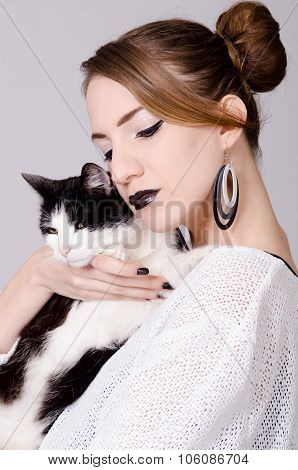 Elegant Lady Holding Black And White Cat With Yellow Eyes