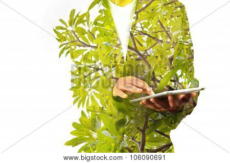 Double Exposure Of Business Man Using Mobile Tablet Pc With Green Leaf