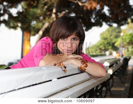 Beautiful Young Woman Sits On A Wooden Bench