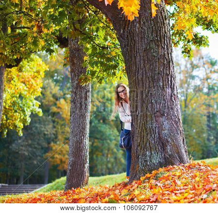 beautiful young woman in autumn park hiding behind a tree
