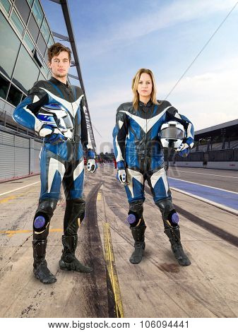 Two young riders, a man and a woman, from the same motorsports team posing in the pits lane of a race track