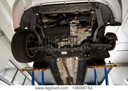 Detail of lifted automobile at repair service station