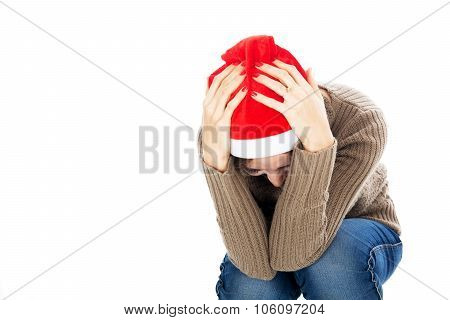 Frustrated Woman In Santa Hat Sitting With His Head In His Hands