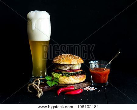 Fresh homemade burger on wooden serving board with spicy tomato sauce, sea salt, herbs and glass of
