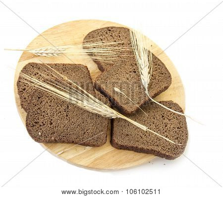 Slices of rye bread on a wooden board and ears of rye