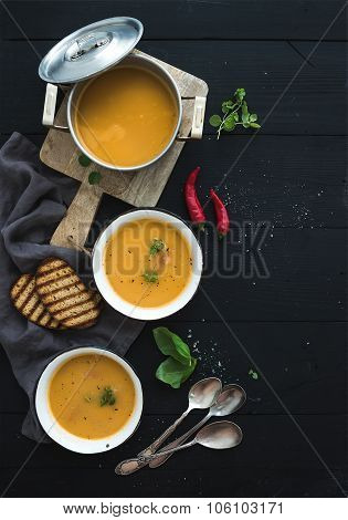 Red lentil soup with spices, herbs, bread in a rustic metal saucepan and bowls, over dark wood backd