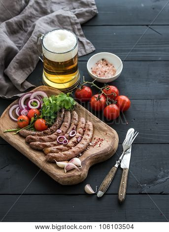 Grilled sausages with vegetables on rustic serving board and mug of light beer over black wooden bac