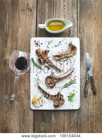 Grilled lamb chops. Rack of Lamb with garlic, rosemary and spices on white serving board, wine glass