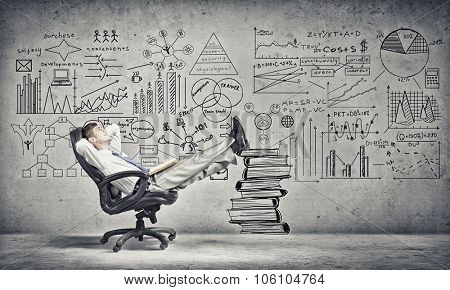 Young handsome businessman sitting in chair with his legs on pile of books
