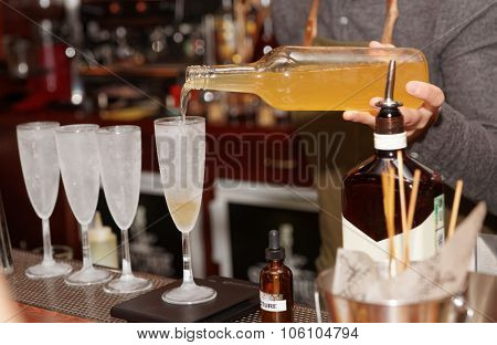 Bartender is pouring liquor in frozen glass