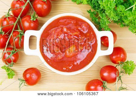 Bowl with chopped tomatoes and parsley on wood
