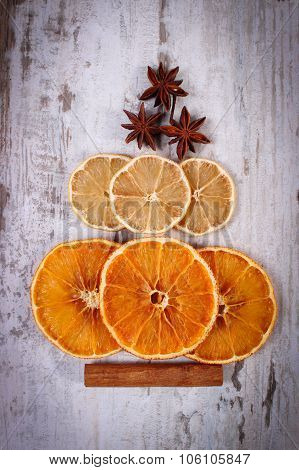 Christmas Tree Shape Made Of Dried Orange, Lemon And Anise On Old Wooden Background