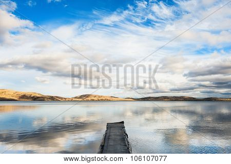 Old Pier On The Lake And The Sky Reflecting In The Water.