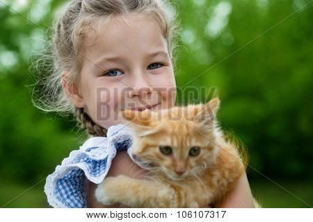 Cute little girl playing with a red kitten