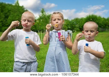 Joyful children inflate soap bubbles outdoors