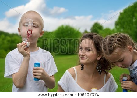 Mother and child blowing soap bubbles in summer park. Sunny day.