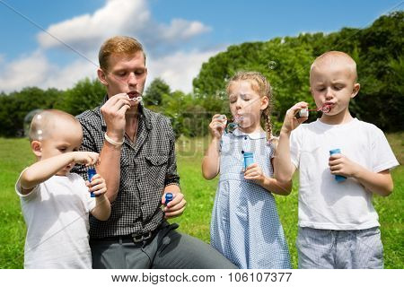 Elder brother teaches the younger brothers and sister blowing bubbles
