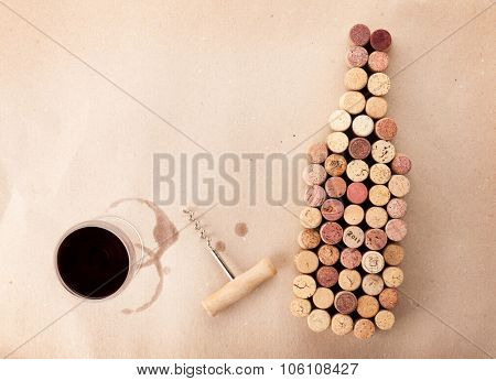 Wine bottle shaped corks, glass of wine and corkscrew over cardboard paper background. View from above with copy space