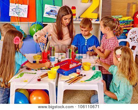 Group children with female teacher in  preschool  kindergarten painting.