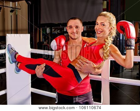 Female boxer with your male coach after workout in gym. Man carry girl in his arms.