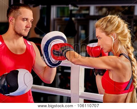 Female boxer  throwing  right cross at mitts with her trainer in ring.