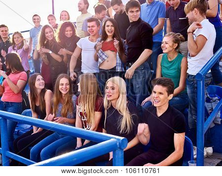 Sport fans beautiful girl and men on tribunes. Group people.