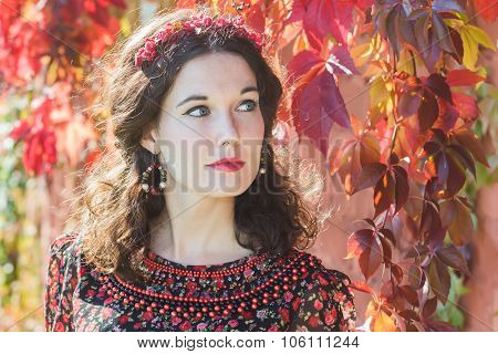 Portrait Of Fairy Autumn Girl With Red Fall Wreath At Red Floral Background Of Parthenocissus Climbi