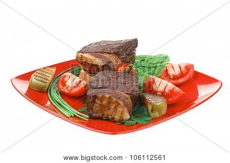 meat food : grilled beef garnished with apples and fresh raw tomatoes with hot pepper over bread slice on red plate isolated over white background