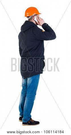 Backview of an engineer in construction helmet stands and using a mobile phone. Standing young guy. Rear view people collection.  backside view of person.  Isolated over white background.