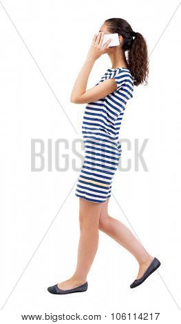 a side view of a woman walking with a mobile phone. beautiful curly girl in motion.  backside view of person.  Rear view people collection. Isolated over white background.