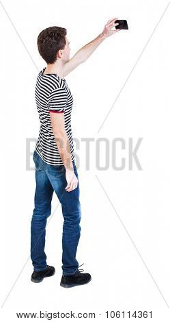 Back view of man with tablet. Standing young guy. Rear view people collection.  backside view of person.  Isolated over white background. The guy in the striped shirt photographed on a mobile phone.