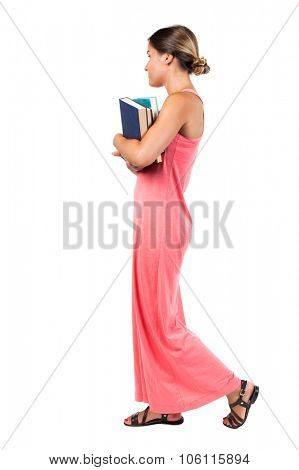 A girl carries a heavy pile of books. side view. Rear view people collection.  backside view of person.  Isolated over white background. girl in a red dress is easy right carrying a stack of books.