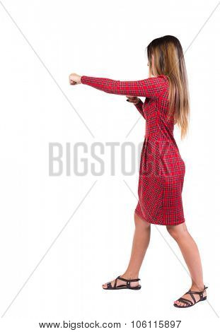 skinny woman funny fights waving his arms and legs. Isolated over white background. Long-haired girl in a red plaid dress hits right hand.