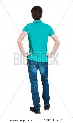 Back view of man in jeans. Standing young guy. Rear view people collection.  backside view of person.  Isolated over white background. A guy in a T-shirt is stylish aquamarine hands on hips.