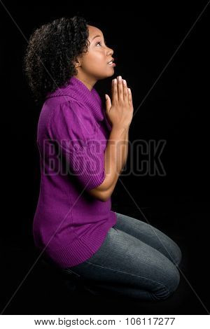 Black woman on knees praying