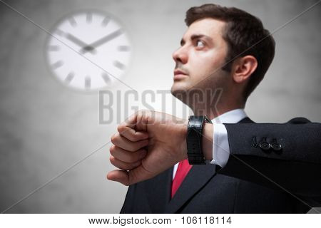 Businessman looking at the watch on the wall