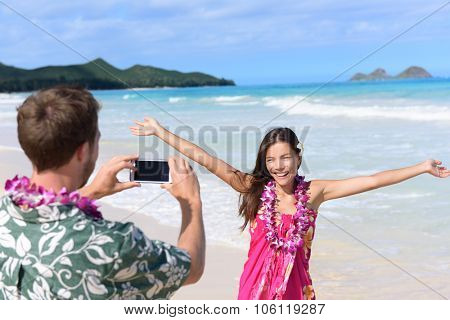 Man taking pictures with smart phone of woman on beach on Hawaii. Young couple having fun living happy lifestyle on Hawaiian beach holiday vacation travel. Man using smartphone for photo.