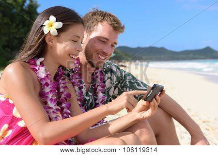 Couple on beach using smart phone app sharing photos on social media on Hawaii with smart phone. Young woman and man in love on beach vacations in Hawaiian clothing flower lei.