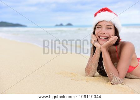 Christmas beach vacation - cute mixed race Asian Chinese girl portrait in Santa hat lying down relaxing posing on white sand in a tropical destination during winter holidays.