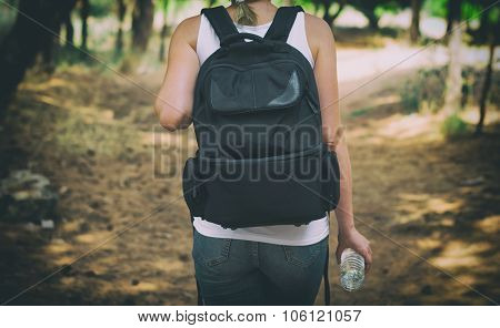 Woman With Backpack In The Forest. View From The Back.