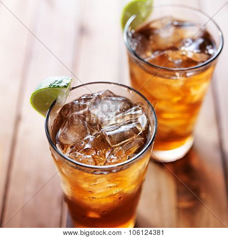 two glasses of iced tea with lime wedges on wooden table close up