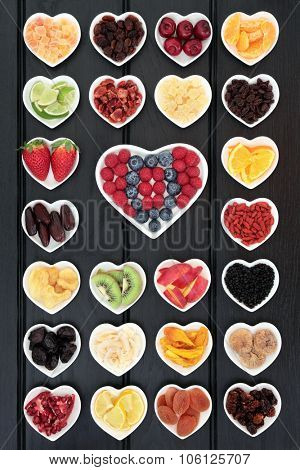 Large mixed fruit background in heart shaped dishes with fruits high in antioxidants, vitamin c and dietary fiber.