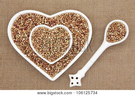 Buckwheat super food in heart shaped bowls and porcelain spoon over hessian background.