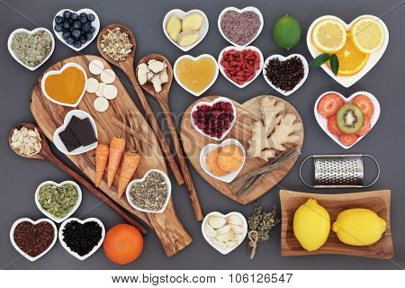 Large health food and herb selection for cold and flu remedy including foods high in antioxidants and vitamin c on olive wood boards and spoons over grey background.